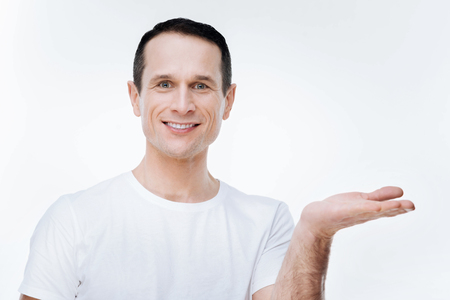 Positive mood. Cheerful nice delighted man smiling and looking at you while holding his hand Stock Photo