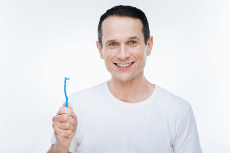 Dental hygiene. Joyful positive happy man holding a toothbrush and smiling while caring about his teeth Stock Photo