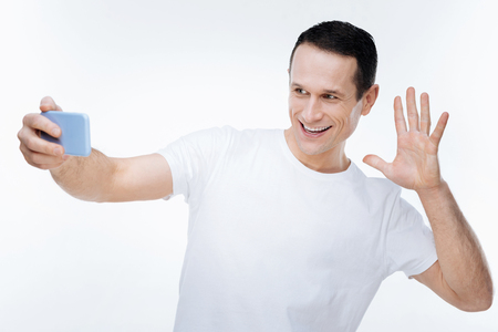 Time for selfies. Happy cheerful nice man smiling and showing his hand while taking selfie with his smartphone Stock Photo