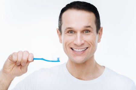 Absolutely healthy teeth. Cheerful nice happy man looking at you and showing his smile while holding a toothbrush