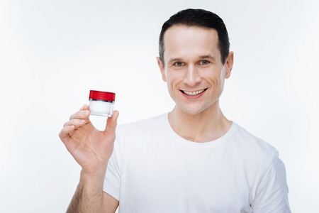 Professional cosmetics. Joyful nice positive man holding a cream bottle and smiling while looking at you Stock Photo