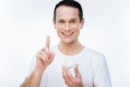 Moisturizing cream. Joyful happy handsome man looking at you and showing you his finger while having moisturizing cream on it 版權商用圖片