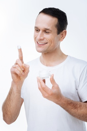Smooth skin. Positive nice handsome man holding a bottle of cream and looking at his index finger while applying the cream on his face