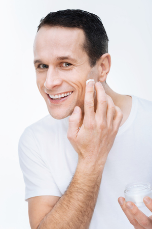 Caring about skin. Delighted happy handsome man smiling and applying moisturizing cream while caring about his skin