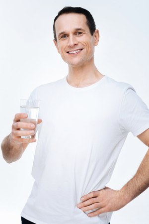 So refreshing. Nice happy well built man standing against white background and holding a glass of water while preparing to drink it Stock Photo