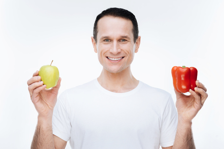 On a diet. Cheerful nice happy msn smiling and looking at you while showing you healthy food Stock Photo