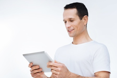 Digital device. Joyful positive young man holding a tablet and looking at its screen while using modern technology