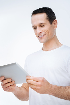 Modern device. Happy cheerful nice man smiling and looking at the tablet screen while surfing on the Internet