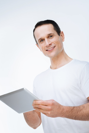 Modern tablet. Delighted nice happy man smiling and looking at you while using a modern tablet