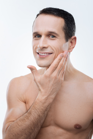 Perfect face. Nice happy delighted man smiling and enjoying the smoothness of his skin while standing against the white background Stock Photo