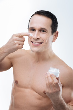 Gentle skin. Positive nice happy man smiling and holding a facial cream bottle while putting cream bottle while putting it on his cheek