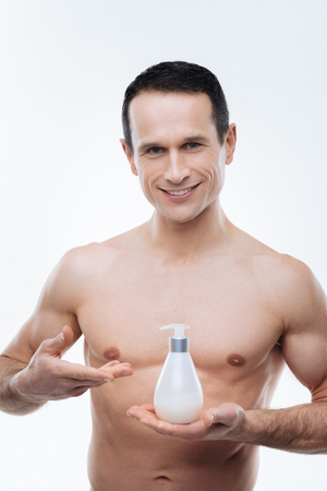 For soft skin. Nice delighted handsome man smiling and looking at you while presenting a high quality body lotion