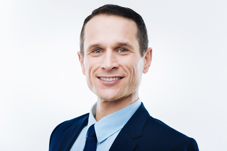 Business success. Portrait of a nice delighted happy businessman smiling while looking at you