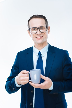 Coffee break. Professional nice smart businessman holding a cup and looking at you while having a coffee break Stock Photo