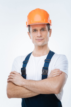 For safety. Confident nice handsome architect wearing a helmet and smiling while looking at you
