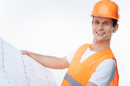 Plan of a building. Smart confident nice engineer wearing a helmet and holding his draft while looking at it