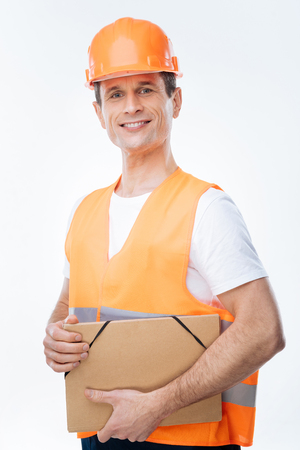 Professional device. Delighted smart professional engineer wearing a uniform and holding his tablet while working on it