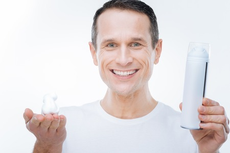 For shaving. Happy joyful nice man looking at you and showing the shaving foam while standing against while background