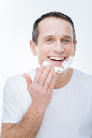 Morning shaving. Joyful handsome young man smiling and putting on shaving foam while being in a good mood Stock Photo