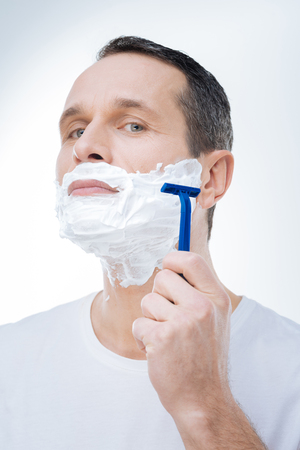 Time to shave. Handsome pleasant adult man looking at you and shaving while caring about his appearance