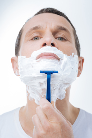 Shaving process. Serious nice handsome man holding up his chin and using a razor while shaving