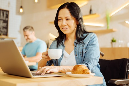 Freelancer. Pretty joyful dark-haired crippled woman sitting in a wheelchair and holding a cup of coffee and working on her laptop and a man sitting in the background