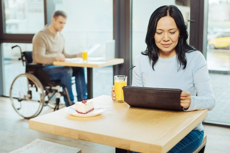 Drinking juice. Beautiful happy dark-haired woman drinking juice and using her tablet while sitting in a cafe and a man in the wheelchair sitting in the background Stock Photo