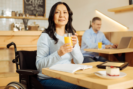 Healthcare. Pretty vigorous disabled woman sitting in a wheelchair and drinking juice and looking in the distance and a man sitting in the background
