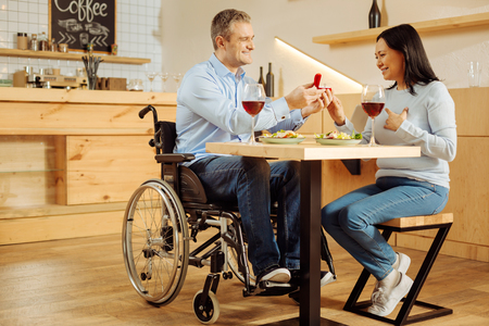 My beloved. Good-looking joyful handicapped man smiling and proposing to his pretty beloved inspired woman and holding a ring while having romantic dinner Stock Photo