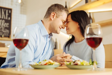 My life. Good-looking loyal well-built man and a beautiful loving dark-haired woman sitting with their eyes closed and holding hands while drinking wine Stock Photo