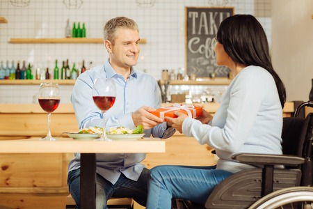 Pampering. Handsome content blond man smiling and giving a present to his pretty joyful disabled woman while having dinner
