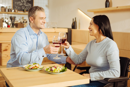 To our love. Handsome gleeful well-built man and a pretty inspired handicapped woman smiling and drinking wine and having dinner