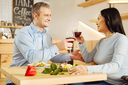Cheers. Attractive alive blond man and a beautiful inspired dark-haired woman smiling and drinking wine and having dinner