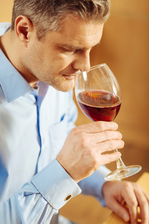 Relaxation. Good-looking concentrated blond man drinking wine and wearing a blue shirt while relaxing