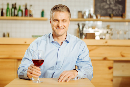 Recreational. Handsome exuberant well-built man drinking wine and wearing a blue shirt while relaxing Stock Photo
