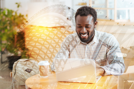 Online communication. Delighted international man expressing positivity while looking at computer leaning arm on the table