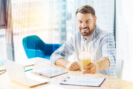 Take it. Handsome male person keeping smile on his face and holding paper cup with coffee while looking at camera
