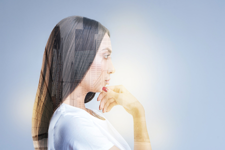 New horizons. Earnest brunette pensive woman standing in profile  and touching her chin while waiting for inspiration