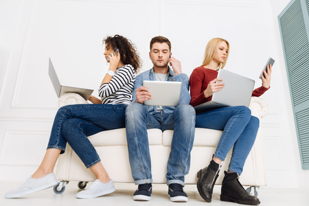 Cozy sofa. Confident girls using their gadgets and being attentive while sitting near their partner