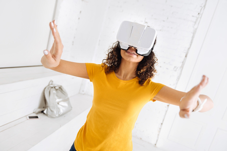Virtual reality. Cheerful brunette keeping smile on her face and raising arms while being in frustration