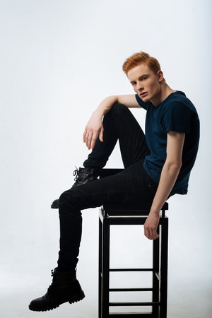 Stony-faced. Handsome concentrated red-haired young man sitting on the chair and putting one foot on it and wearing a black t-shirt and trousers and boots