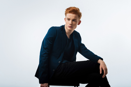 Train of thoughts. Good-looking stern dark-eyed red-haired young man wearing a black jacket and thinking and sitting on the chair