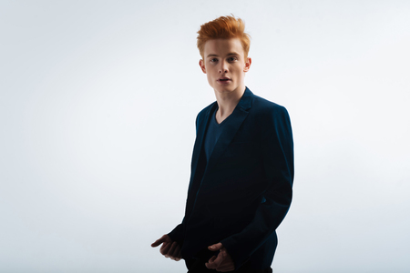 Hottie. Good-looking stony-faced young red-headed man wearing a jacket and having a serious expression on his face and looking in the distance Stock Photo