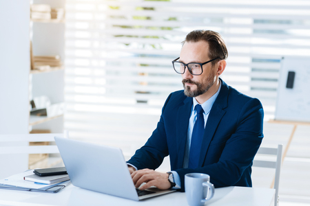 Modern technology. Handsome professional appealing  businessman typing response while sitting and looking at the screen Stock Photo