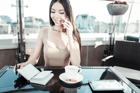 Business conversation. Beautiful occupied pleasant girl sitting on in the rooftop restaurant making notes and talking on the telephone.