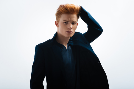 Hottie. Attractive stern red-headed young man wearing a black jacket and touching his hair and looking in the distance