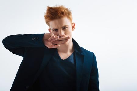 나쁜 소년. 검은 자 켓을 입고 그의 입으로 그의 손가락을 닫고 쳐다보고 잘 생긴 unsmiling 빨강 머리 젊은 남자 스톡 콘텐츠