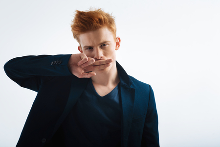 Bad boy. Good-looking unsmiling red-headed young man wearing a black jacket and closing his mouth with his fingers and staring