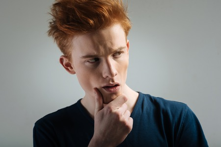 Making a decision. Handsome thoughtful red-haired young man thinking and looking in the distance and touching his chin Standard-Bild
