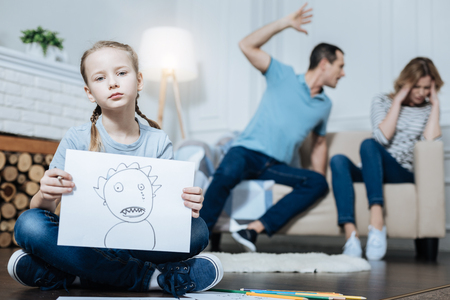 My drawing. Unsmiling blue-eyed little girl showing a picture and sitting on the floor while her father beating her mom